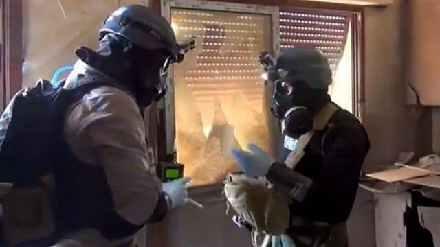 Zwei Personen mit Gasmasken bei einer Untersuchung.