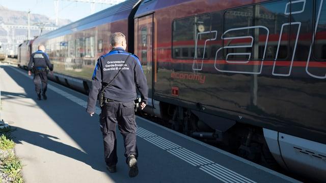 Zwei Grenzwächter stehen vor einem Zug.