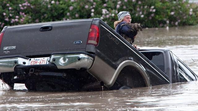 Ein Mann auf einem Auto, das im Wasser versinkt