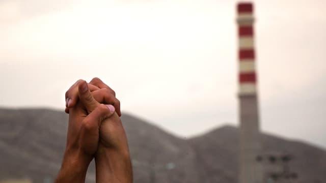 Aufnahme zweier Hände vor dem Hintergrund einer Industrieanlage. Die Hände sind gefaltet und gegen den Himmel gereckt.