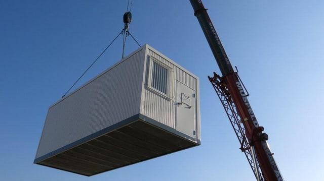 Ein Gefängniscontainer schwebt am Halteseil eines Krans in der Luft