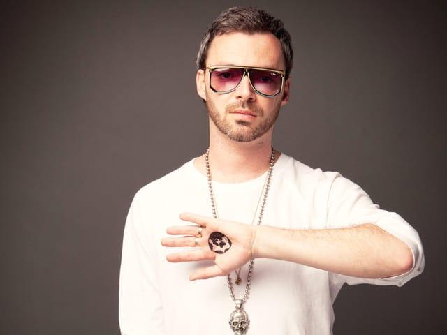 Ein Rapper mit Kette und weissem Pulli trägt eine eckige Sonnebrille.