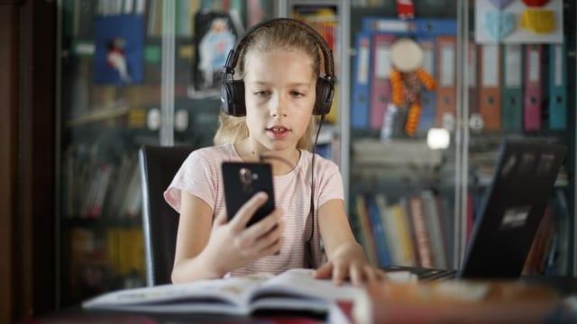 Ein Mädchen mit Kopfhörern und einem Smartphone sitzt vor einem Schulbuch.