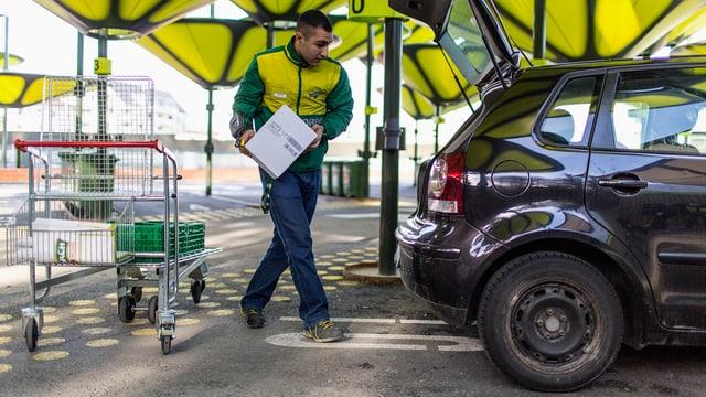 Ein Angestellter von LeShop trägt Lebensmittel ein den Kofferraum eines Kundenfahrzeuges.