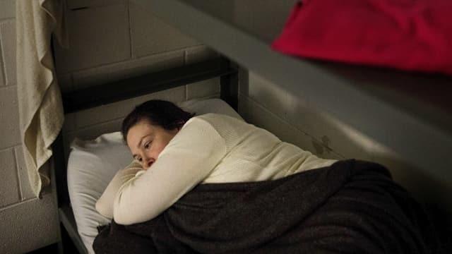 Eine nachdenkliche Frau im Bett ihrer Zelle.