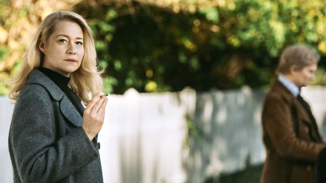 Eine Frau steht rauchend in einem Mantel vor einem Gartenzaun, nachdenklich zur Seite blickend.