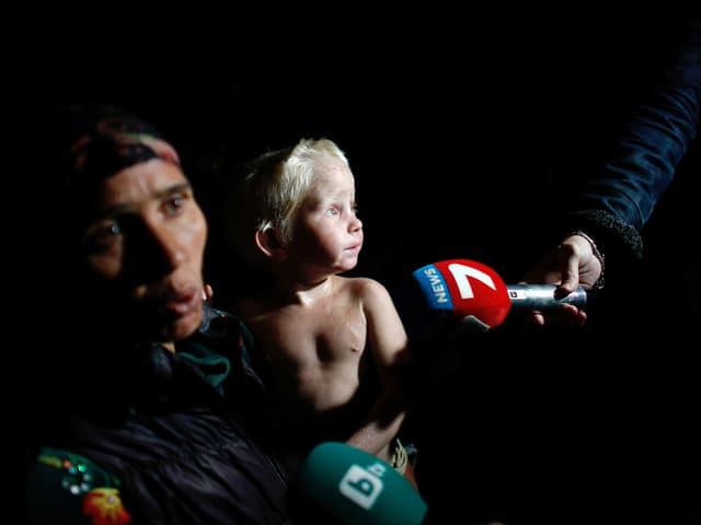 Vor schwarzem Hintergrund sitzt ein nacktes Kind auf dem Schoss einer Frau, Mikrofone von Fernsehstationen werden davor gehalten.