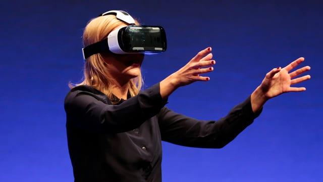 Frau mit virtueller Brille streckt die Arme nach vorne.