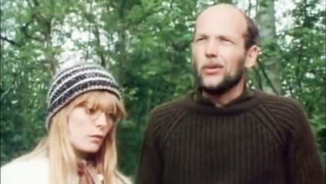 Eine Frau mit langen blonden Haaren und einer Wollmütze auf dem Kopf, neben ihr ein Mann mit brunem Pullover.