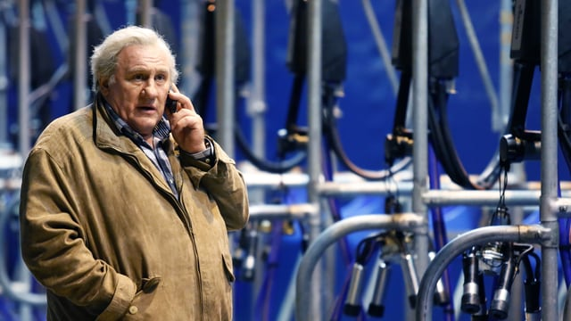 Gérard Depardieu telefoniert vor einer grossen Melkmaschine.