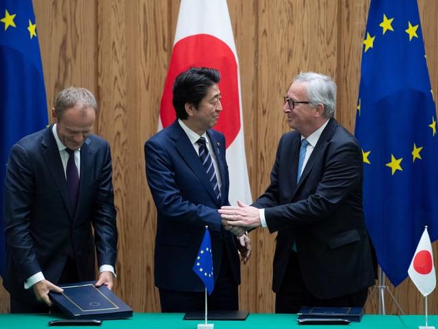 Tust, Shinzo Abe und Juncker stehen hinter dem Tisch. Juncker gibt Shinzo Abe die Hand.