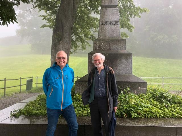 Zwei Männer vor einem Steindenkmal.