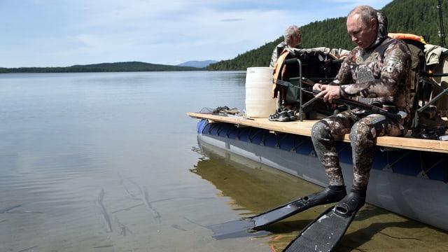 Putin sitzt auf dem Rand eines Schiffs in Taucherausrüstung.