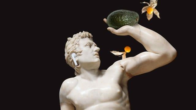 Marmorstatue mit Airpod im Ohr und Avocado in der Hand
