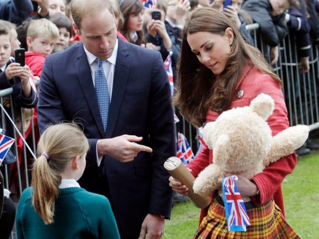 Kate und William nehmen den Schotten-Bär für ihren Sohn entgegen. Davor steht ein Mädchen mit grünem Pulli.