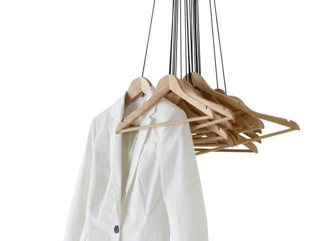 Kleiderbügel hängen an Kordeln an der Decke, an einem Bügel hängt ein Blazer