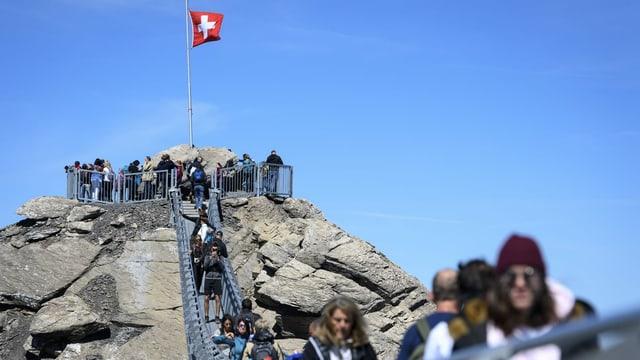 Touristen gehen über die Hängebrücke im Diablerets-Massiv der Berner Alpen.