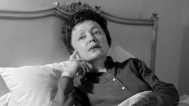 Edith Piaf liegt im Bett.