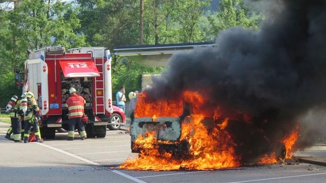 Brennendes Auto und Feuerwehrfahrzeug.