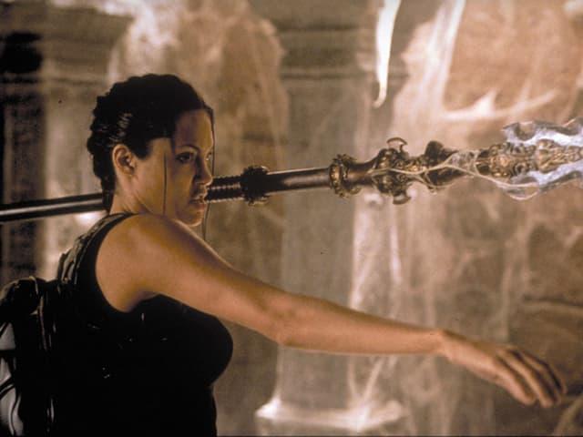 Angelina Jolie als Lara Croft zeigt sich wehrhaft mit einem Speer.