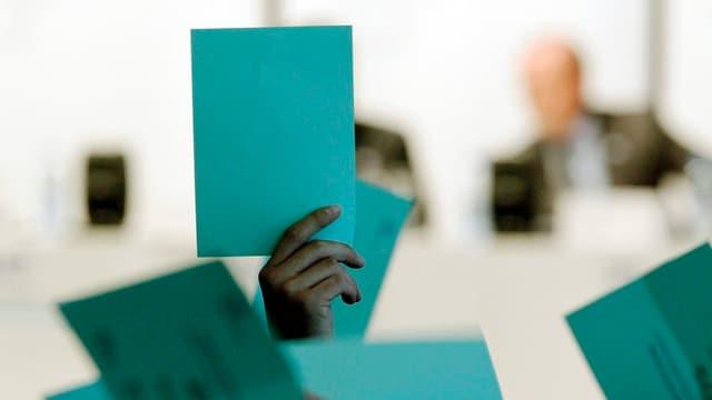 Eine Hand hält einen Wahlzettel in die Luft.
