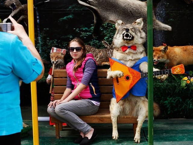 Eine Frau lässt sich mit einem ausgestopften Wolf mit Fliege und Weste, der Laute spielt, fotografieren.