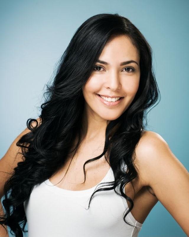 Frau mit langen braunen Haaren und Locken lacht in Kamera.