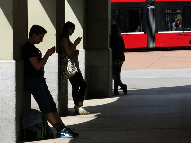 Zwei Teenager stehen in einer Laube und schauen auf ihr Smartphone.