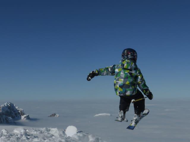 Wolkenloser Himmel, im Vordergrund ein Kind, das mit Skiern vom Berg herunter zu springen scheint. Tief unten ist das Nebelmeer zu sehen, heraus ragen ein paar Berggipfel.
