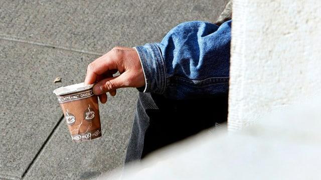 Eine Hand hält einen Pappbecher.