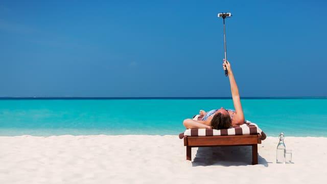 Ein Mann kiegt auf einer Liege am Strand und fotografiert sich selbst mit einer Selfie-Stange.