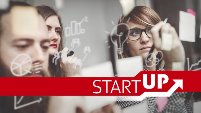 Schriftzug Startup, zwei Frauen ein Mann nah