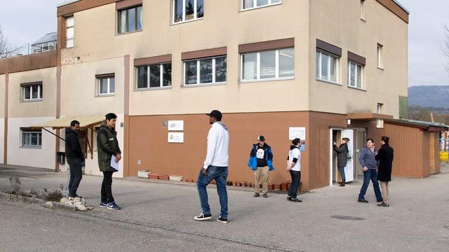 Symbolbild: Männer vor einem Haus.