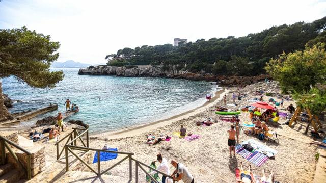 Kleine Sandstrandbucht mit Touristen und Meer