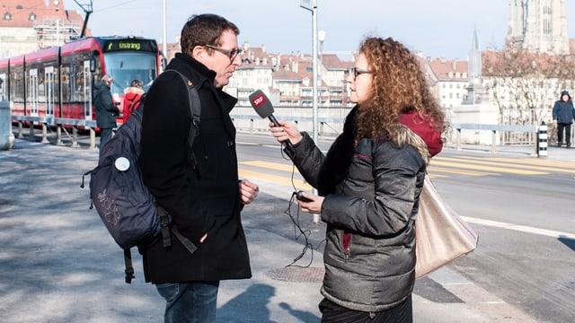 Eine Frau hält einem Mann auf der Strasse ein Mikrophon vor den Mund.