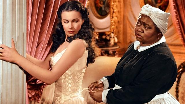 Filmszene: Eine Schwarze schnürt der Hauptdarstellerin das Korsett zu