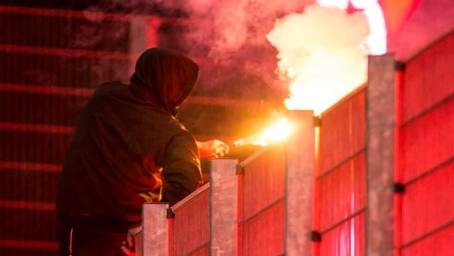 Fussballhooligan mit einer Pyrofackel in der Hand.