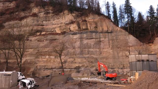 Eine Felswand mit einem Fluss - mehrere Bagger holen Gesteinsmassen aus dem Wasser