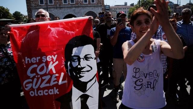 Menschen mit Flagge des Kandidaten.