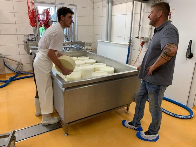 Zwei Männer bei der Käseherstellung in einem Gespräch.