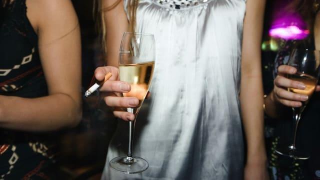 Junge Frau mit einer Zigarette und einem Glas Champagner.