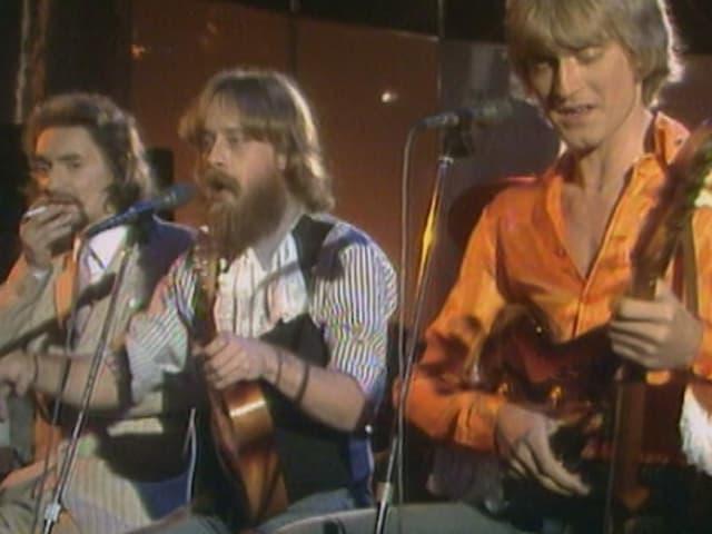 Vier Studenten mit Bart und langen Haaren spielen Ukulele während TV- Show.