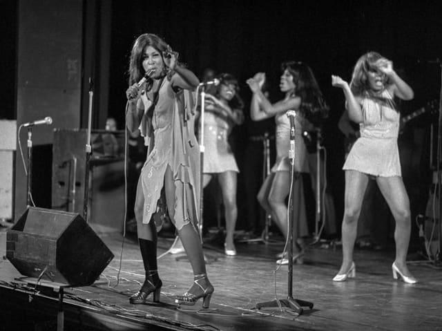 Schwarzweiss-Aufnahme von Tina Turner auf der Bühne zusammen mit Tänzerinnen.