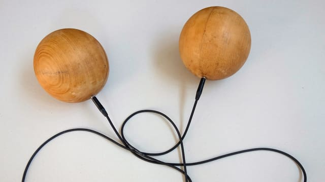 Zwei Holzkugeln, die mit einem Gitarrenkabel verbunden sind.