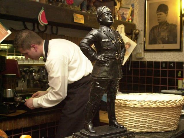 Die Bronzestatue des Duce steht auf dem Tresen, an der Wand ein Foto von Mussolini und im Hintergrund der Kellner an der Kaffeemaschine.