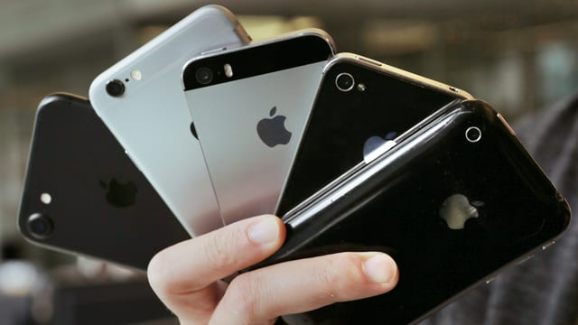 Eine frau hält Smartphones in der Hand.