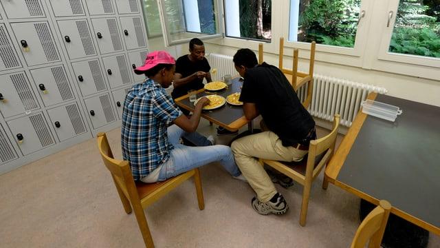 Drei schwarze junge Männer sitzen um einen Tisch und essen.