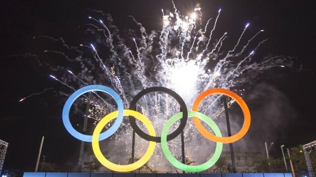 Olympische Ringe mit Feuerwerk im Hintergrund