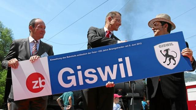 Die neue Tafel des Bahnhofs Giswil in den Händen der zb -Spitze.