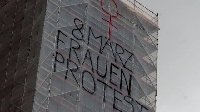 Das eingerüstete Fraumünster mit einem Protest-Schriftzug.